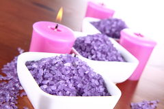 Spa salt. Lavender spa salt and lavender candles on a wooden background Stock Image