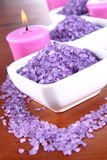 Spa salt and candles. Lavender spa salt and lavender candles on a wooden background stock image