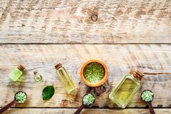 Spa salt and lotions for skin with tea tree oil on rustic wooden background top view pattern copyspace Stock Image