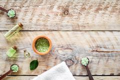 Spa salt and lotions for skin with tea tree oil on rustic wooden background top view pattern copyspace Royalty Free Stock Images
