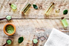Spa salt and lotions for skin with tea tree oil on rustic wooden background top view pattern copyspace Royalty Free Stock Image