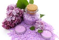 Spa sammansättning av den lila stearinljus, flaskan och blommor Arkivbild