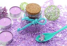 Spa sammansättning av den lila stearinljus, flaskan och blommor Arkivbilder