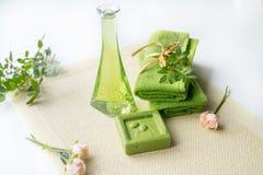 Spa sats: vätsketvål, salt hav, grön handduk, nya blommor, olivsidor på en gammal gul servett på en vit bakgrund Royaltyfria Bilder