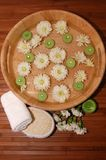 Spa Scene. Floating green candles, chrysanthemum, towel, bath sponge, body lotion on a bamboo mat Royalty Free Stock Photos