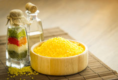 Spa sea salt and aromatherapy oil. Wooden bowl full of yellow sea salt and bottles with aromatherapy oil and colored salt on bamboo table Stock Image