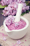 Spa sea salt in mortar and lilac flowers. Stock Image