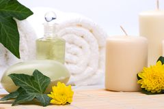 Spa set. Chrysanthemums flowers, aroma candles, oils, organic soap on bamboo mat and towels with ivy leaves over white background best suited for relaxing and Stock Photos