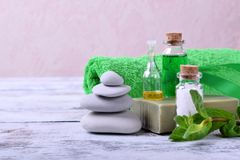 Spa set: massage stones, aromatic oil, sea salt, green gel, organic soap and green towel. On white wooden table royalty free stock photos