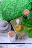 Spa set: massage stones, aromatic oil, sea salt, green gel, organic soap and green towel. On white wooden table stock images