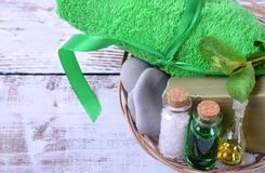 Spa set: massage stones, aromatic oil, sea salt, green gel, organic soap and green towel. On white wooden table royalty free stock photography