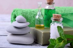 Spa set: massage stones, aromatic oil, sea salt, green gel, organic soap and green towel. On white wooden table stock photos