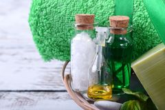 Spa set: massage stones, aromatic oil, sea salt, green gel, organic soap and green towel. On white wooden table stock photo