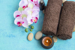 Spa set with orchid flower, towels and candle  on painted wooden Royalty Free Stock Image