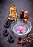 Spa set. Orchid flowers in a bowl with water, stones Zen, Buddha statue and massage oils Royalty Free Stock Image