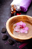Spa set. Orchid flowers in a bowl with water, zen stones and massage oils Stock Photos