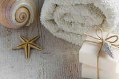 Spa set products-two soap bars, soft towels and sea shells on wooden background with space for text Stock Photos