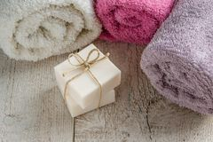 Spa set products-two soap bars, soft towels and sea shells on wooden background with space for text Stock Image