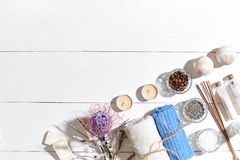 Spa set with sea salt, essential oil, soap and towel decorated with dry flower on white wooden background Royalty Free Stock Image