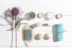 Spa set with sea salt, essential oil, soap and towel decorated with dry flower on white wooden background Stock Photos