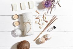 Spa set with sea salt, essential oil, soap and towel decorated with dry flower on white wooden background Stock Image