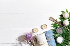 Spa set with sea salt, essential oil, soap and towel decorated with dry flower on white wooden background Stock Images