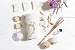 Spa set with sea salt, essential oil, soap and towel decorated with dry flower on white wooden background Royalty Free Stock Photos