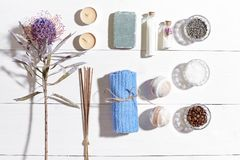 Spa set with sea salt, essential oil, soap and towel decorated with dry flower on white wooden background Stock Photography