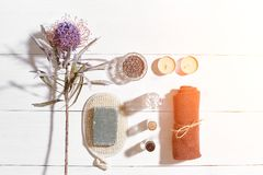 Spa set with sea salt, essential oil, soap and towel decorated with dry flower on white wooden background. Sun flare Royalty Free Stock Images