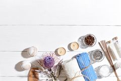 Spa set with sea salt, essential oil, soap and towel decorated with dry flower on white wooden background Stock Photo