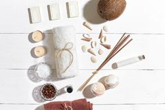 Spa set with sea salt, essential oil, soap and towel decorated with seashells on white wooden background Royalty Free Stock Images