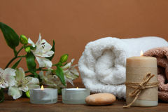 Spa set. Sea salt, towel and candle on a wooden table on a brown background Stock Images