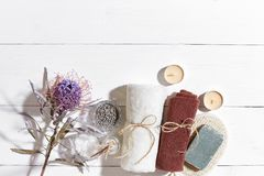 Spa set with soap and towel decorated with dry flower on white wooden background Royalty Free Stock Photo