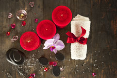 Spa set. Top view: candles, massage stones, towel on natural bac Stock Photos