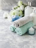 Spa set on a white marble table with a stack of towels, selective focus Stock Image