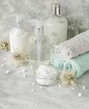 Spa set on a white marble table with a stack of towels, selective focus Royalty Free Stock Photo