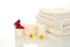 Spa setting. Four candles and a butterfly near bath towels Royalty Free Stock Photography
