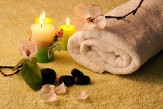 Spa setting. Image of a towel, candles, flower and black stones to give impression of pure and simple natural beauty and spa treatment ingredients Stock Images