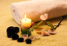 Spa setting. Image of a towel, candles, flower and black stones to give impression of pure and simple natural beauty and spa treatment ingredients Royalty Free Stock Photography