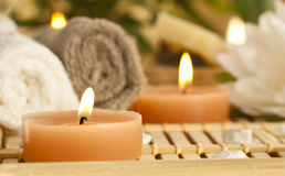 Spa setting. With candles, waterlily and pebbles Royalty Free Stock Photography