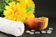 Spa setting. Image of spa concept with three candles, towel, orange flowers, and glass stones Stock Image