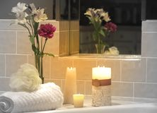 Spa Setting. Lit candles, fresh flowers, and bathing supplies next to tub Stock Images