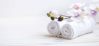 SPA setting with bath towels and orchid flower, selective focus. SPA setting with bath towels and orchid, selective focus Royalty Free Stock Photo