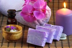Spa setting with beauty products soap and bath salt. Candle burning, pebble, a orchid, a bottle with oil, soap, and more royalty free stock photo