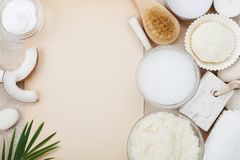 Spa setting from body care, wellness and beauty treatment. Coconut scrub, oil and cream on stone table top view. Empty sheet for recipe. Flat lay Stock Image