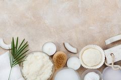 Spa setting from body care, wellness and beauty treatment. Coconut scrub, oil and cream on stone table top view. Flat lay. Spa setting from body care, wellness royalty free stock photography