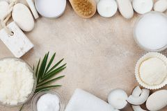 Spa setting from body care, wellness and beauty treatment. Coconut scrub, oil and cream on stone table top view. Flat lay style. royalty free stock image