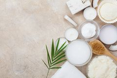 Spa setting from body care, wellness and beauty treatment. Organic coconut scrub, oil and cream on stone table top view. Flat lay. Spa setting from body care royalty free stock photography