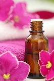 SPA setting with candles, aroma oil and violets Royalty Free Stock Photos