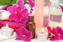 SPA setting with candles, aroma oil and violets. SPA setting with candles, aroma oil and fresh violets Stock Photos
